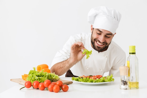 Joyful chef man in cook hat smiling and posing with vegetable salad at work isolated over white wall