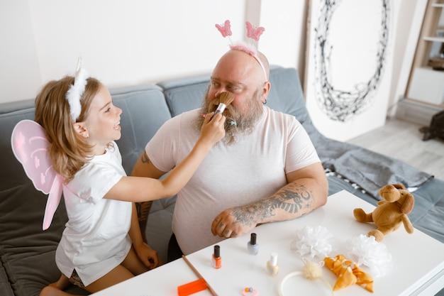 Радостный ребенок наносит пудру на лицо отца, играя в салоне красоты дома