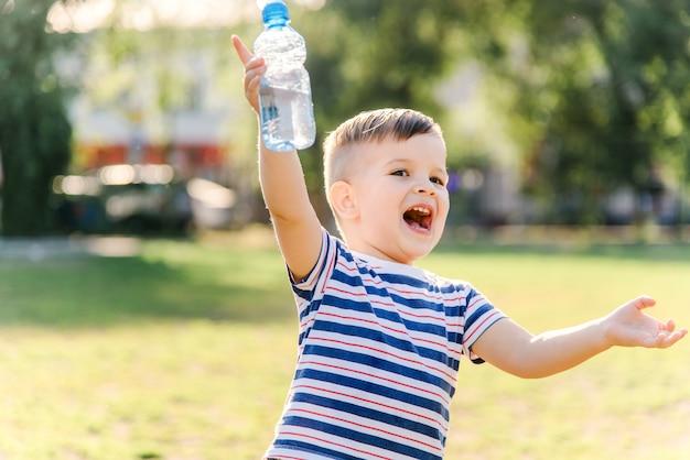 Радостный ребенок пьет чистую воду из бутылки в солнечный день на природе