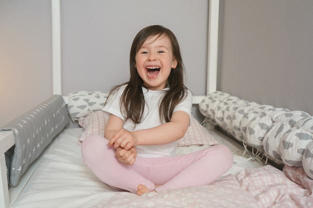 うれしそうな子供がベッドの準備をしています。赤ちゃんはベッドに座って喜んでいます