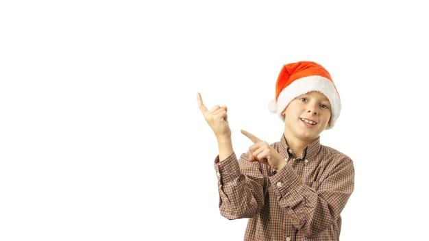サンタクロースのうれしそうな子供は、白い背景で隔離の指でポイントをキャップします。クリスマスセール、割引のコンセプト。バナー