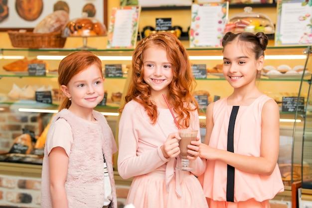 Joyful children stand in a cafe