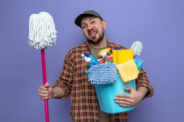Uomo allegro delle pulizie che tiene in mano attrezzature per la pulizia e mop