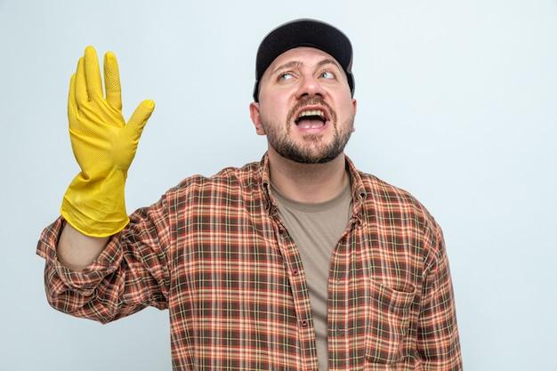 Uomo allegro delle pulizie con guanti di gomma in piedi con la mano alzata