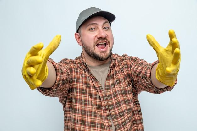 Uomo allegro delle pulizie con guanti di gomma che allungano le mani