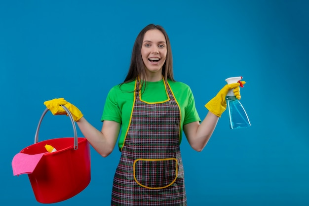 격리 된 파란색 벽에 청소 도구와 스프레이를 들고 장갑에 유니폼을 입고 즐거운 청소 젊은 여자 무료 사진