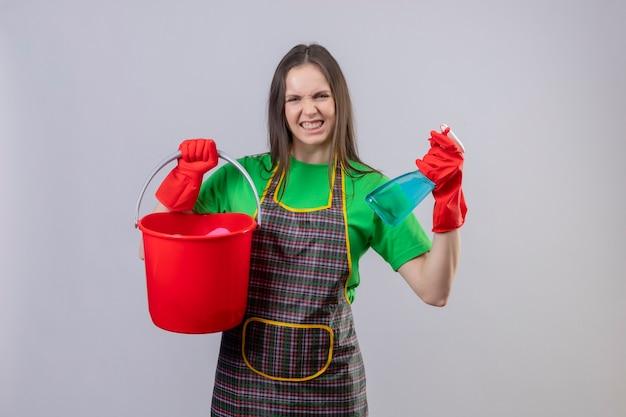 Радостная уборщица молодая женщина в униформе в красных перчатках держит ведро и чистящий спрей на изолированной белой стене