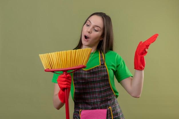 モップを保持し、孤立した緑の壁に歌を歌う赤い手袋で制服を着てうれしそうな掃除若い女性