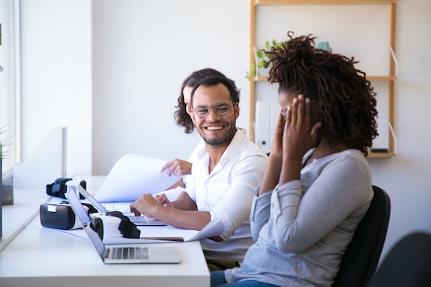 Joyful colleagues laughing during work