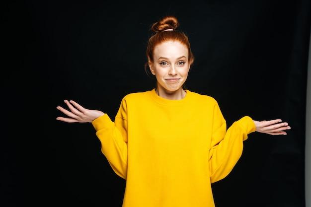 孤立した黒い背景に肩をすくめる黄色のセーターを着てうれしそうな混乱した若い女性
