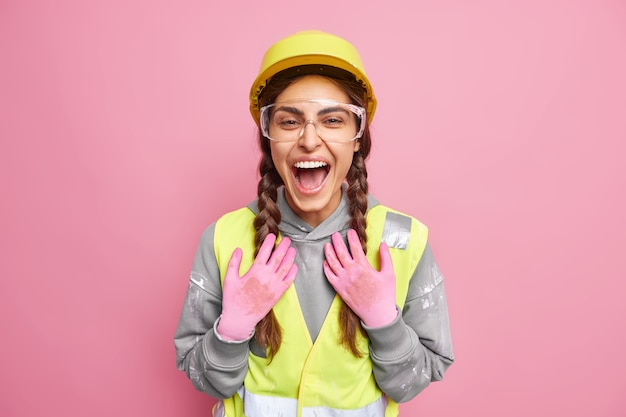 Joyful construction woman prepares for reconstruction building inspects site wears protective glasses hat gloves laughs positively satisfied with results of work. job occupation maintenance.
