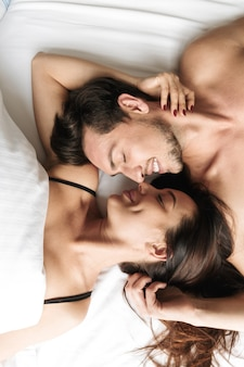 Joyful couple 30s hugging together, while lying in bed at home or hotel apartment