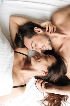 집이나 호텔 아파트에서 침대에 누워있는 동안 함께 포옹하는 즐거운 커플 30 대