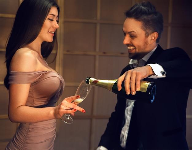 シャンパンで何かを祝ううれしそうなカップル。休日とお祝いのコンセプト。
