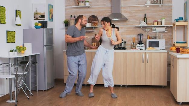 パジャマを着てキッチンで朝食時に踊ったり歌ったりする楽しいカップル。のんきな妻と夫が笑って楽しんで面白い人生を楽しんでいる本物の既婚者ポジティブ幸せな関係