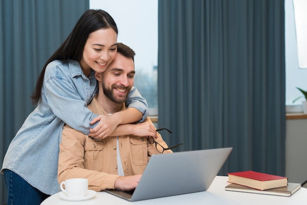 Joyful couple at desk with laptop