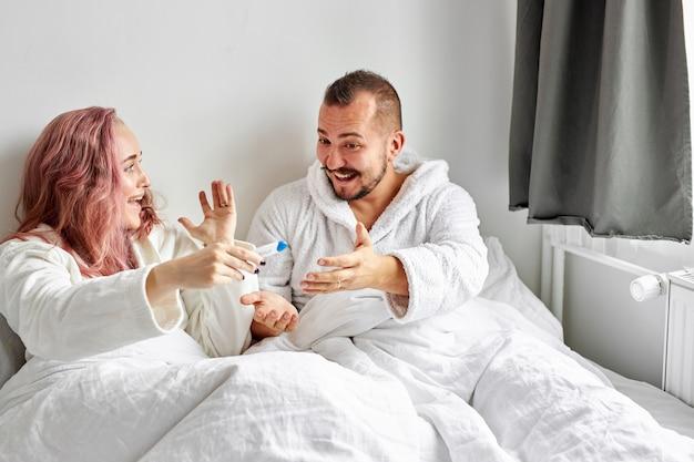 ベッドに横たわって自宅で妊娠検査の結果を見つけるうれしそうなカップル