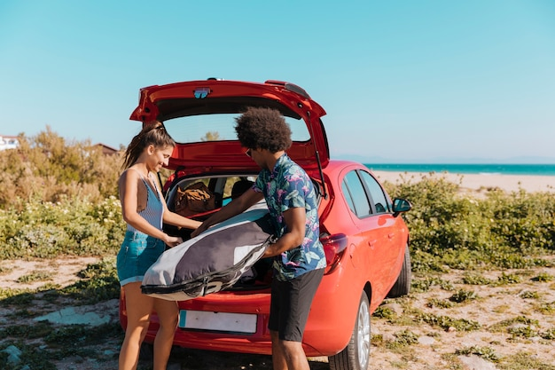 Joyful couple getting things out of trunk on beach