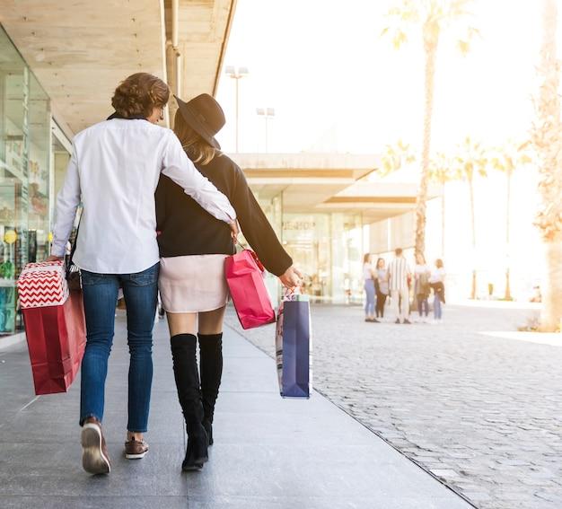 Радостная пара идет по улице с сумок