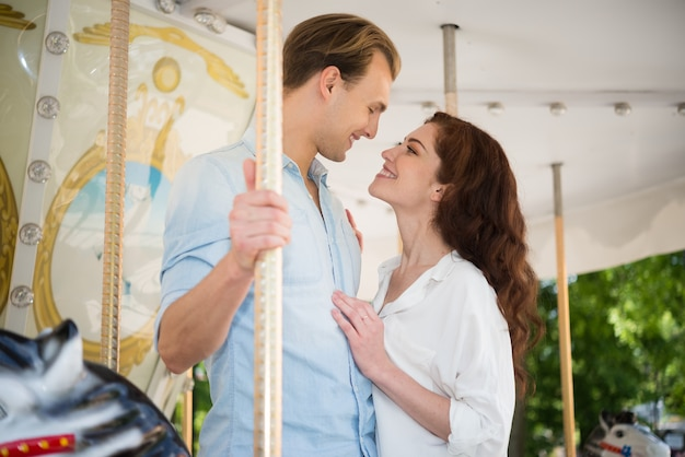 Joyful couple having fun on a carousel