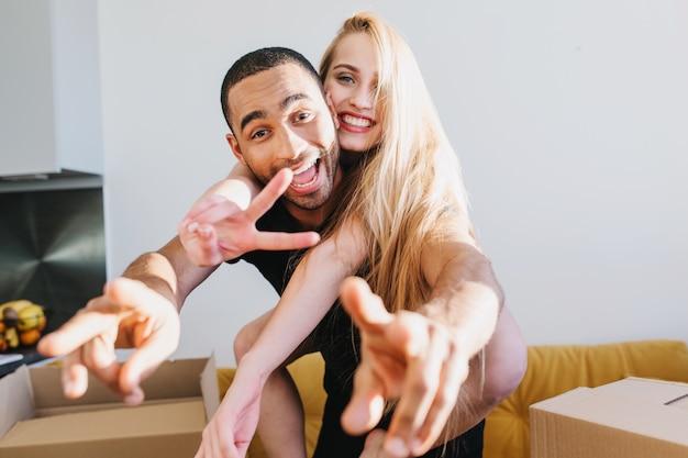 Радостная пара веселится в новом доме, только что купила квартиру, квартиру, распаковывает коробки со своими вещами. молодая девушка сидит на спине мужчины, они показывают мир.
