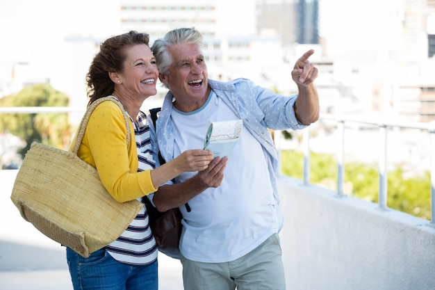 Joyful couple holding map