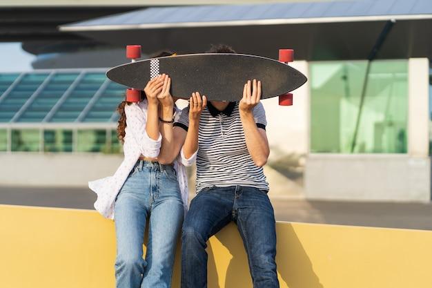 Joyful couple kiss hiding above longboard playful man and woman in love together hold skateboard