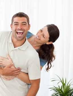 Joyful couple laughing together in the livingroom