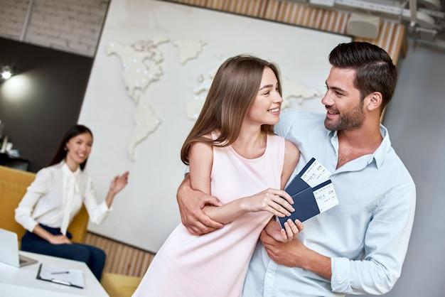 Радостная пара смотрит друг на друга и держит паспорт с авиабилетами