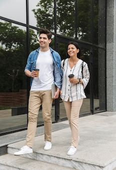 Joyful couple man and woman in casual clothes drinking takeaway coffee while strolling through city street