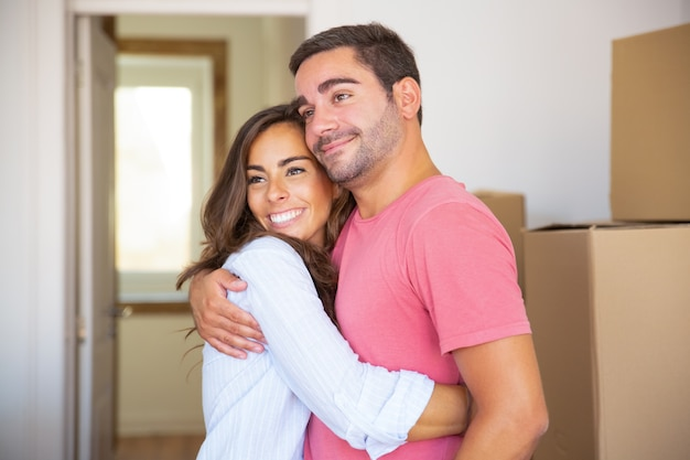 Joyful couple moving into new house, standing among carton boxes and hugging