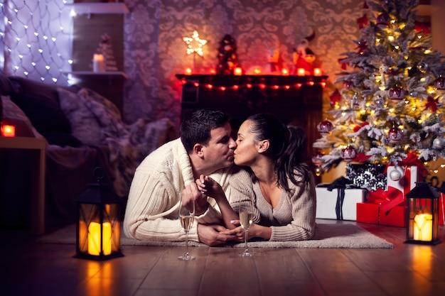 ロマンチックな照明のクリスマスツリーと暖炉の近くのうれしそうなカップル。幸せなカップル。