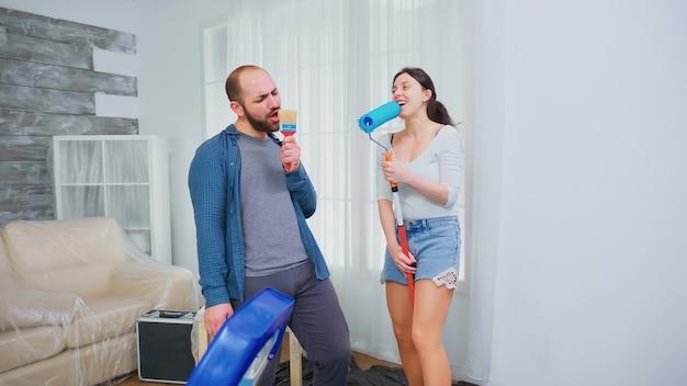 Радостная пара ремонтирует гостиную квартиры. украшение дома, кисть, совместная работа. отделка и ремонт дома в уютной квартире, ремонт и косметический ремонт.