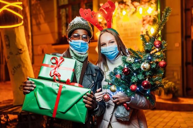 Радостная пара стоит вечером в городе с рождественскими подарками в медицинских масках