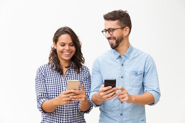 Joyful couple using smartphones