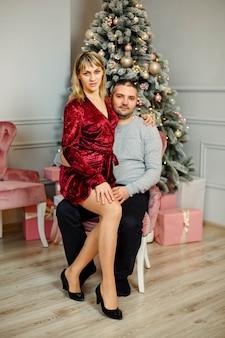 Радостные уютные моменты зимних праздников. сезонные поздравления. стильная счастливая пара улыбается