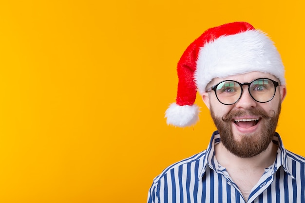 Joyful crazy cute young hipster male in red santa claus hat posing over yellow wall. the concept of christmas and the new year..
