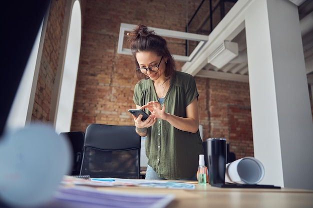 스마트폰을 사용하여 안경을 쓰고 웃고 있는 즐거운 창의적인 여성 인테리어 디자이너 또는 건축가