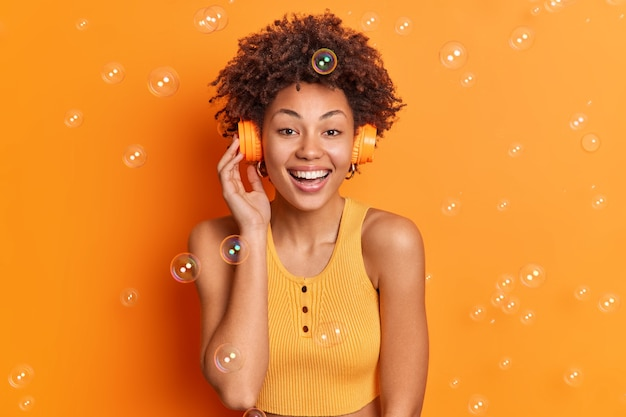 Joyful curly girl enjoys listening music via wireless headphones smiles gently enjoys spare time dressed in casual top isolated over orange wall soap bubbles flying around