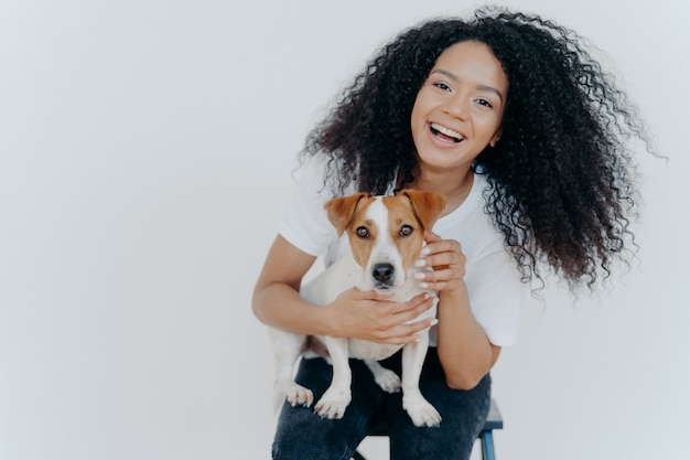 Joyful curly girl petting her dog, rejoicing buying jack russell terrier,