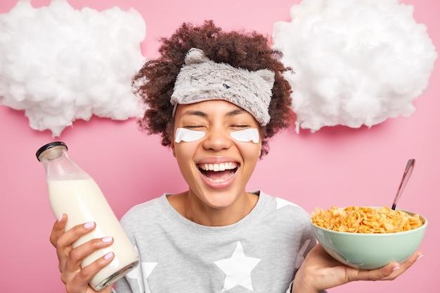 うれしそうな縮れ毛のエスニック女性が目を閉じて笑顔が広く健康的な朝食をとる良い睡眠がパジャマを着て目の下にパッチを当てるピンクの壁に孤立したポジティブな感情を表現する