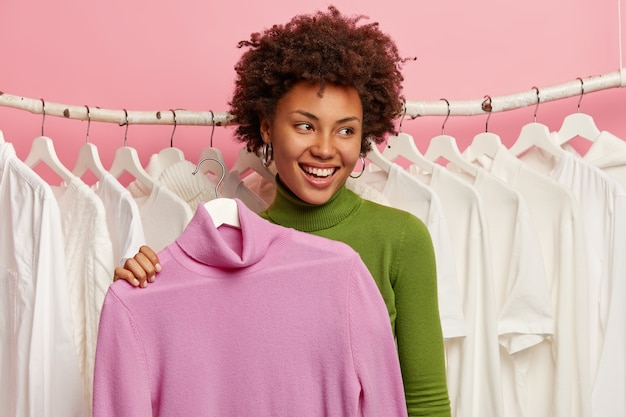 Радостная кудрявая женщина покупает наряд, держит на вешалке водолазку, примеряет в гардеробной, занимается покупками, смотрит в сторону с улыбкой, стоит в мастерской, носит зеленый полонек. шоппинг образ жизни
