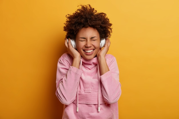 Joyful curly haired woman enjoys every bit of favorite song, listens music in stereo headphones, closes eyes and smiles broadly, inspired with awesome music, dressed in casual wear, stands indoor