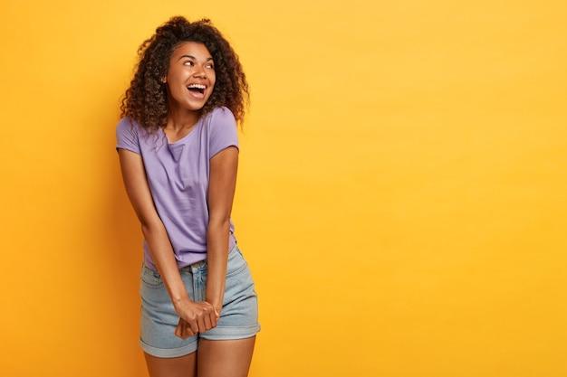 Gioiosa donna dai capelli ricci tiene le mani unite, ride felice, concentrata da parte, indossa una maglietta viola e pantaloncini di jeans, si sente felice e spensierata