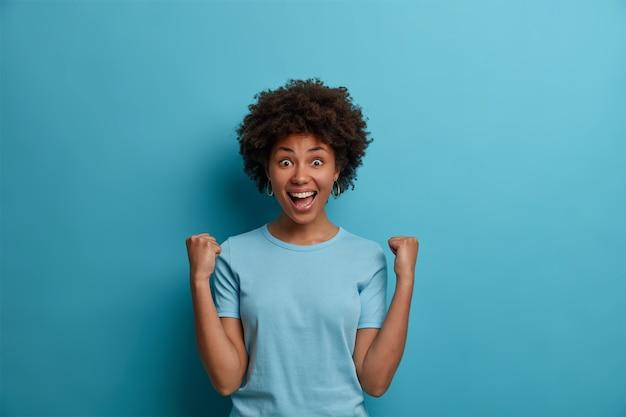 즐거운 곱슬 머리 여자는 큰 기회를 얻고 기뻐하고, 주먹을 부딪 히고, 좋은 소식을 축하하고, 좋은 소식을 축하하고, 즐겁게 웃으며, 행복으로 가득 찬 눈으로 응시하고, 실내 포즈를 취합니다.