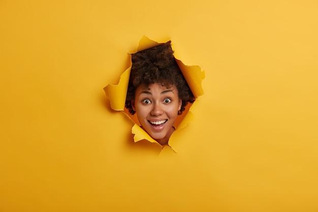 Gioiosa giovane donna dai capelli ricci mantiene la testa nel buco della carta strappata, guarda nello sfondamento del muro, sorride ampiamente, mostra i denti bianchi perfetti
