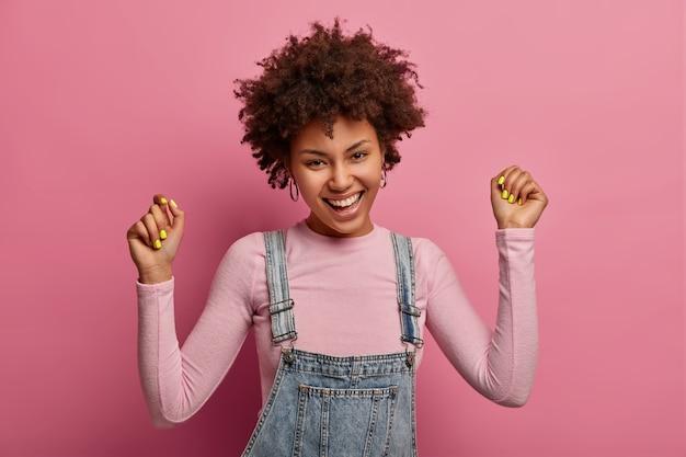 Радостная кудрявая молодая женщина поднимает руки, подтягивает насос, радостно улыбается, одета в повседневную одежду, в приподнятом настроении, громко смеется, позирует на фоне розовой пастельной стены, чувствует себя победителем