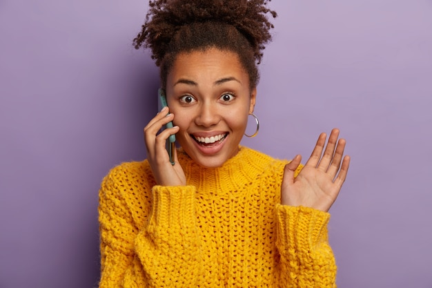 Joyful curly young woman speaks on phone, glad to hear good news, gestures during conversation, raises palm, wears earrings and yellow sweater, enjoys casual talk, isolated over purple background