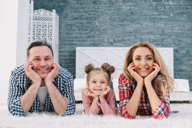 Joyful cute family lying on carpet looking at camera