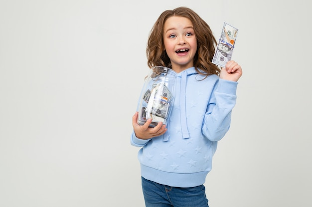 Joyful cute girl with a glass jar and money on a white wall with blank space.